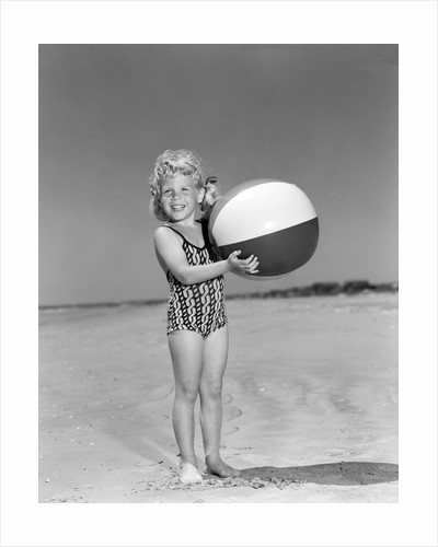 1950s smiling little girl standing on beach holding beach ball looking at camera by Corbis