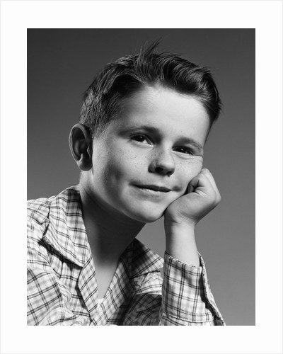 1950s child portrait boy with freckles posed resting head cheek on hand by Corbis