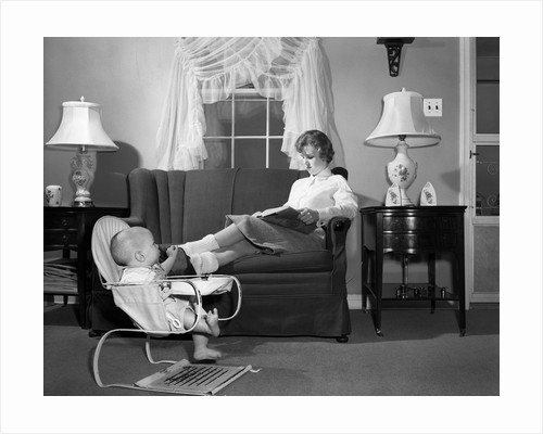1950s teen babysitter seated on sofa reading schoolbook while baby in bouncy sling chair grabs her propped up foot by Corbis