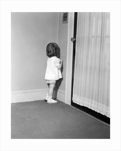 1950s 1960s little girl in white dress being punished standing in a corner by Corbis