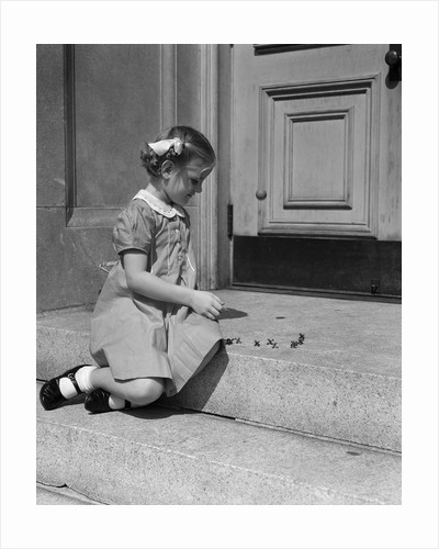 1930s 1940s child little girl sitting on stoop playing jacks by Corbis