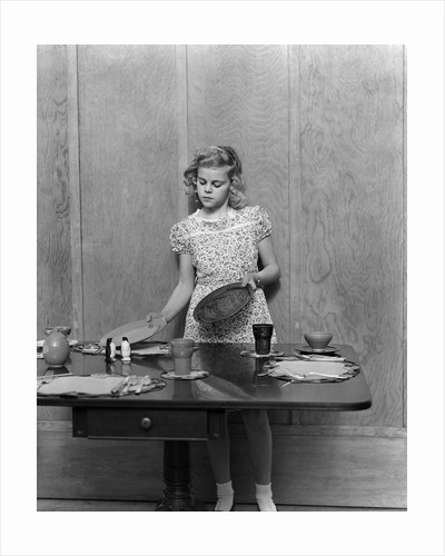 1940s blond pre-teen young woman setting table by Corbis