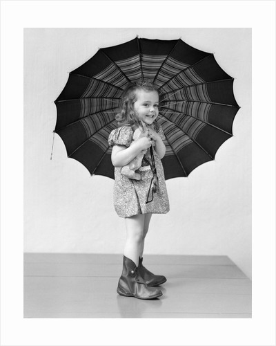 1930s 1940s child smiling little girl holding rainy day umbrella by Corbis