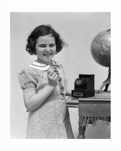 1930s child smiling girl putting money coin into toy cash register bank by Corbis