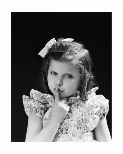 1950s child serious little girl pressing finger to lips hush be quiet secret by Corbis