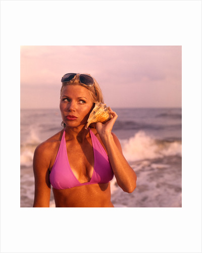 1970s pouting sexy woman in lavender bikini sunglasses near beach surf holding seashell to ear listening to ocean by Corbis