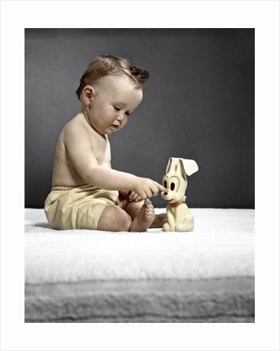 1940s 1950s baby sitting touching toy dog by Corbis