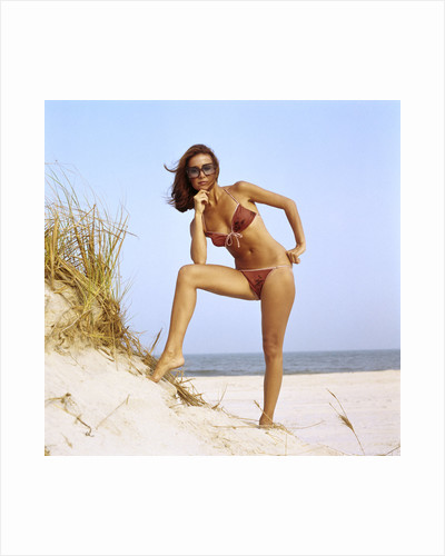 1970s woman wearing two piece string bikini bathing suit sunglasses posing by grassy sand dune at beach by Corbis