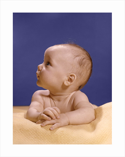 1960s portrait of baby on yellow blanket resting on folded arms head turned to right looking up by Corbis