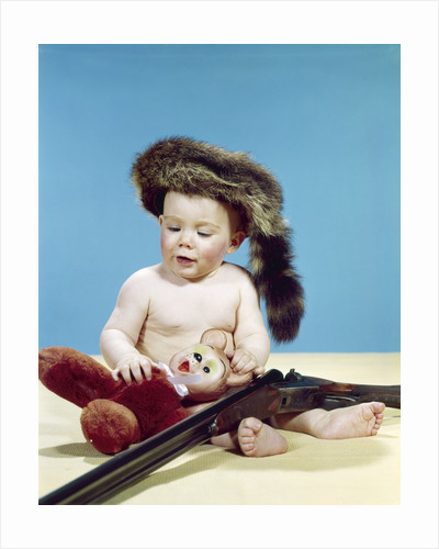 1960s baby boy wearing coonskin cap with stuffed animal and shotgun by Corbis