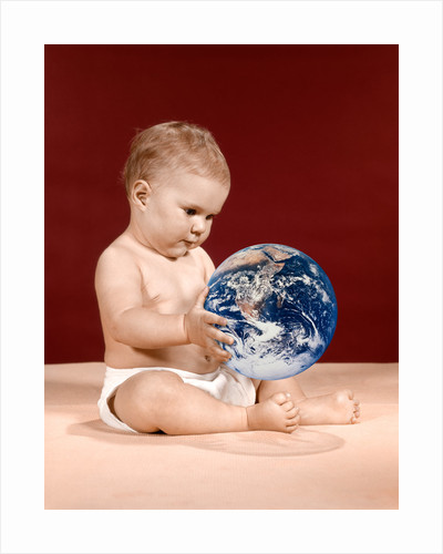1960s symbolic ecology serious baby wearing cloth diapers sitting holding looking at the earth by Corbis