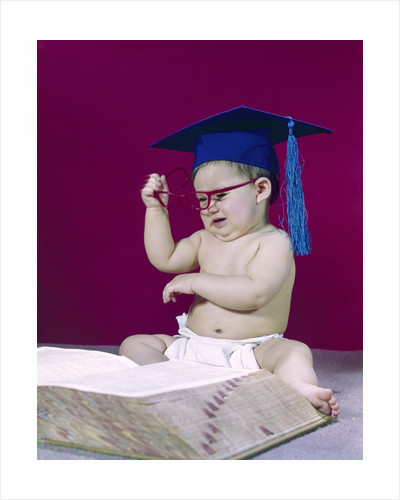 1960s graduate baby wearing mortarboard eyeglasses reading book by Corbis