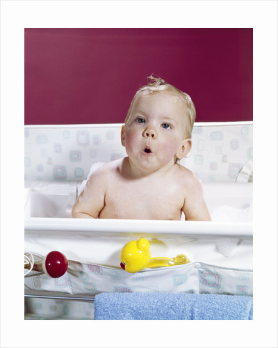 1960s baby in layette bath making funny face by Corbis