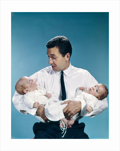 1960s father holding twin babies infants looking down at one of them by Corbis