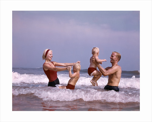 1970s family father mother two sons laughing hand holding jumping in ocean surf at beach having fun together by Corbis