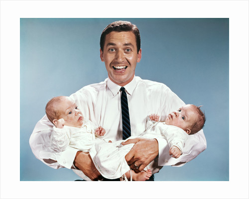 1960s smiling man father looking at camera holding twin babies infants by Corbis