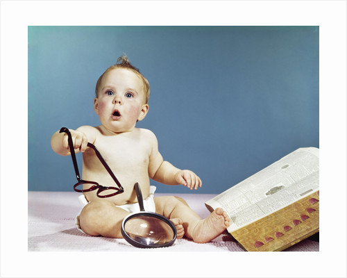 1960s baby holding eyeglasses with open dictionary and magnifying glass research by Corbis