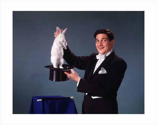 1960s 1970s man magician tuxedo pulling rabbit out of top hat magic illusion sleight of hand trick by Corbis