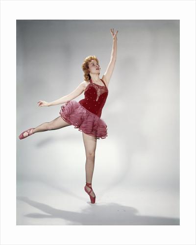 1960s awkward teen girl red velvet costume pink net tutu attempting arabesque en pointe by Corbis