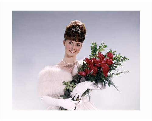 1960s woman prom queen wearing white evening dress holding bouquet of flowers red roses looking at camera by Corbis