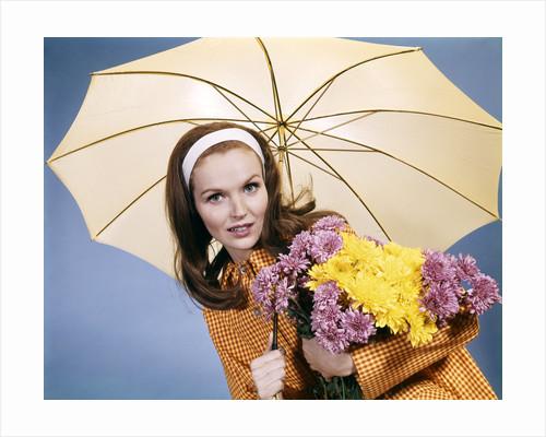 1960s smiling brunette woman holding bouquet autumn flowers chrysanthemums under umbrella red yellow rain coat by Corbis