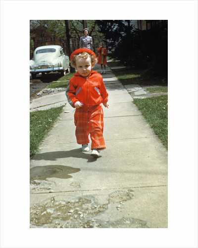 1950s little boy in red outfit running on pavement with mother just behind by Corbis