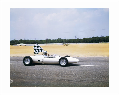 1960s race car driver in lotus ford car taking victory lap holding checkered flag by Corbis