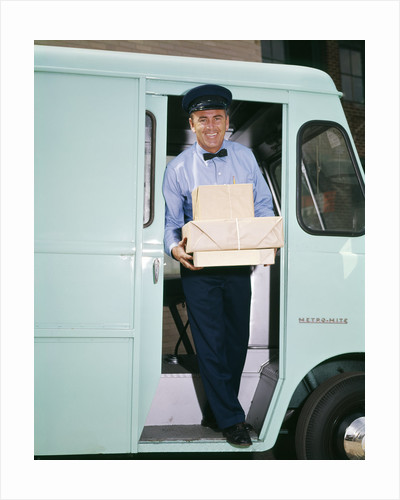 1950s 1960s man driver delivery truck van step out vehicle door holding packages boxes uniform hat service deliver work by Corbis
