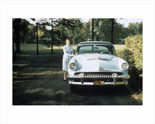 1950s 1955 woman standing beside 1954 mercury automobile by Corbis