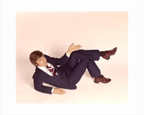 1970s overhead looking down at man lying down legs crossed wearing business suit shrug off hand expression looking at camera by Corbis