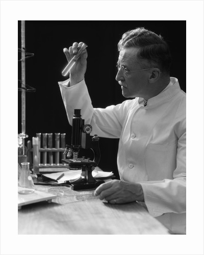 1920s 1930s 1940s scientist lab technician in white coat looking at test-tube in front of microscope by Corbis