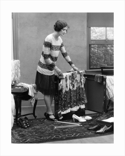 1920s woman packing clothes for travel by Corbis
