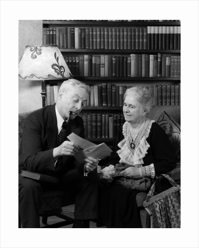 1930s 1940s retired senior couple looking at check in living room man smoking pipe by Corbis