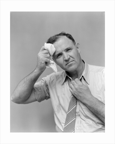 1940s 1950s perspiring man in rolled up shirt sleeves loosening tie holding handkerchief wiping forehead looking at camera by Corbis