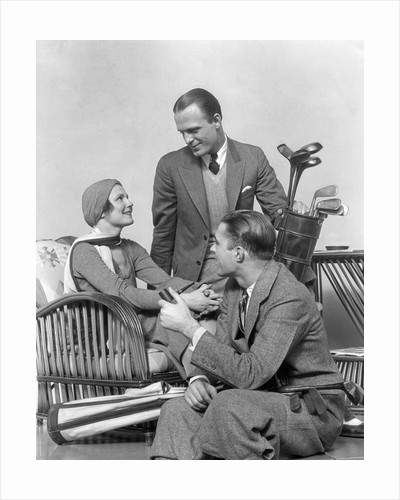 1930s two men one woman golf clubs bag smiling talking sitting bamboo chair man smoking pipe by Corbis