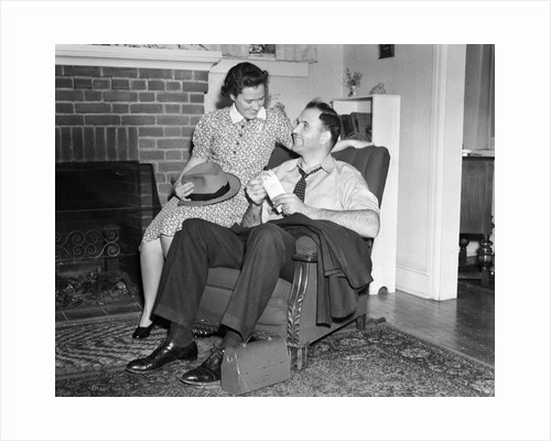 1940s smiling man sitting in chair holding pay envelope while wife sits on arm of chair holding his hat lunch box oriental rug by Corbis