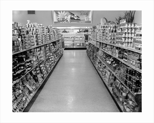 1950s grocery store aisle with canned goods on shelves to either side by Corbis