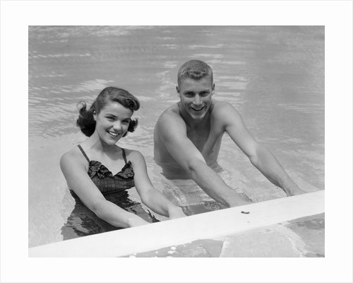 1950s teen couple in swimming pool smiling looking at camera by Corbis