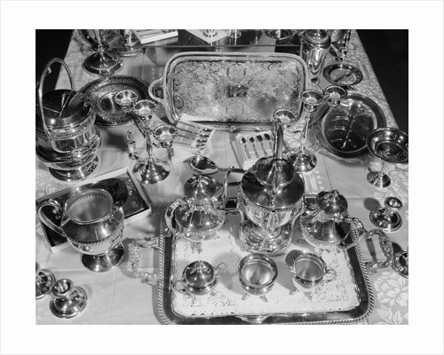 1950s still life overhead view of assortment of silver service pieces including tea set candlesticks & ice bucket by Corbis