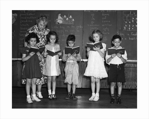 1930s line-up of 5 elementary school students in front of blackboard reading books with teacher looking on by Corbis
