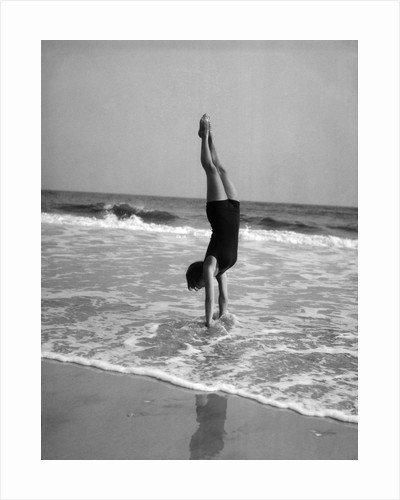 1920s woman doing a handstand in ocean surf by Corbis