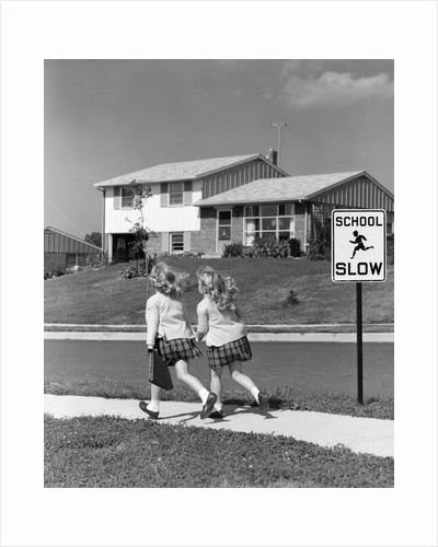 1950s back view of twin girls in plaid skirts & cardigans holding book bags running past school slow sign by Corbis