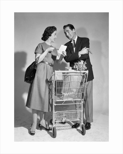 1950s couple man woman shopping cart reviewing grocery list man has cigar in hand by Corbis