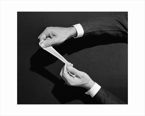 1930s 1940s man's hands symbolic money stretching a dollar by Corbis