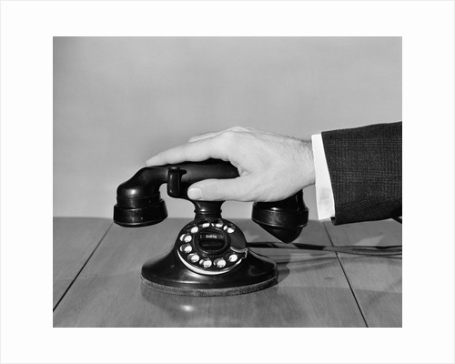 1930s 1940s man's hand on telephone by Corbis