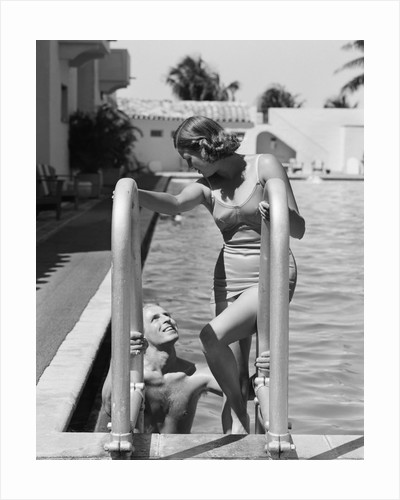 1930s woman wearing one piece bathing suit climbing out of swimming pool looking down at man smiling by Corbis
