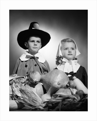 1950s boy & girl in pilgrim costumes with harvest arrangement on table by Corbis