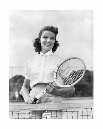 1950s 1940s woman posing with tennis racket on tennis court near net by Corbis
