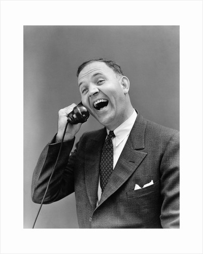 1930s man in suit laughing talking on telephone by Corbis