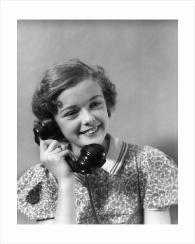 1930s teen girl smiling brunette print dress talking on telephone by Corbis